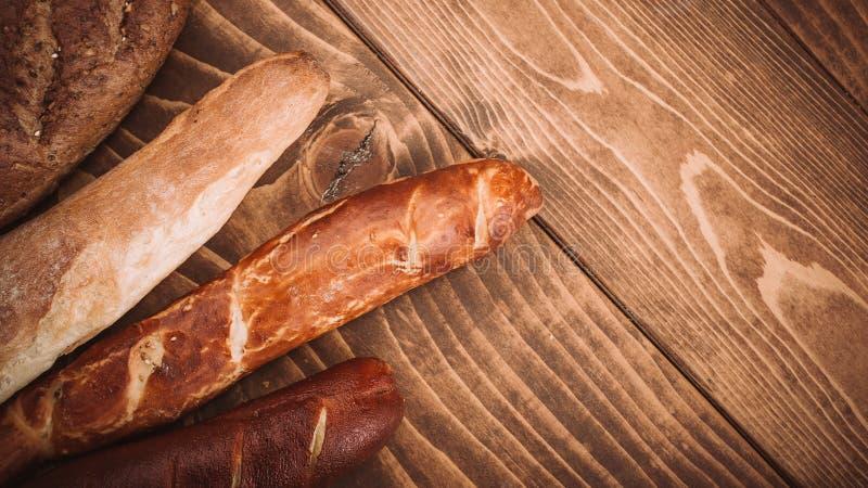 Muchos mezclaron los panes y los rollos cocidos en la tabla de madera rústica fotos de archivo