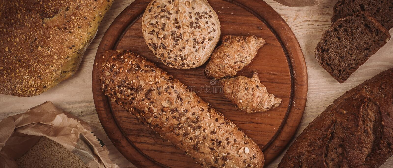 Muchos mezclaron los panes y los rollos cocidos en la tabla de madera rústica imágenes de archivo libres de regalías