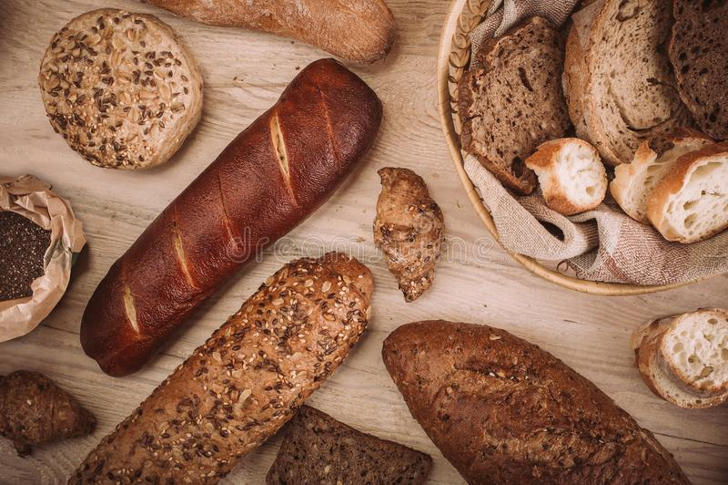 Muchos mezclaron los panes y los rollos cocidos en la tabla de madera rústica imagen de archivo