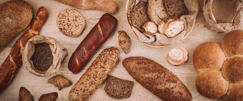 Muchos mezclaron los panes y los rollos cocidos en la tabla de madera rústica fotografía de archivo libre de regalías