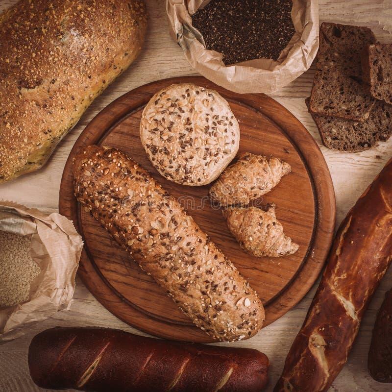 Muchos mezclaron los panes y los rollos cocidos en la tabla de madera rústica imagenes de archivo