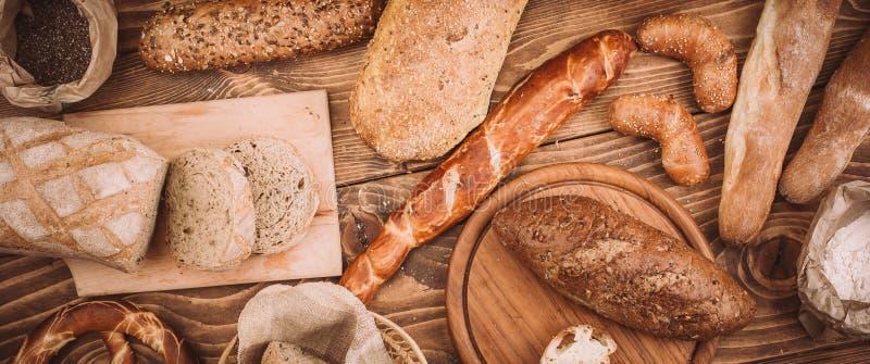 Muchos mezclaron los panes y los rollos cocidos en la tabla de madera rústica foto de archivo