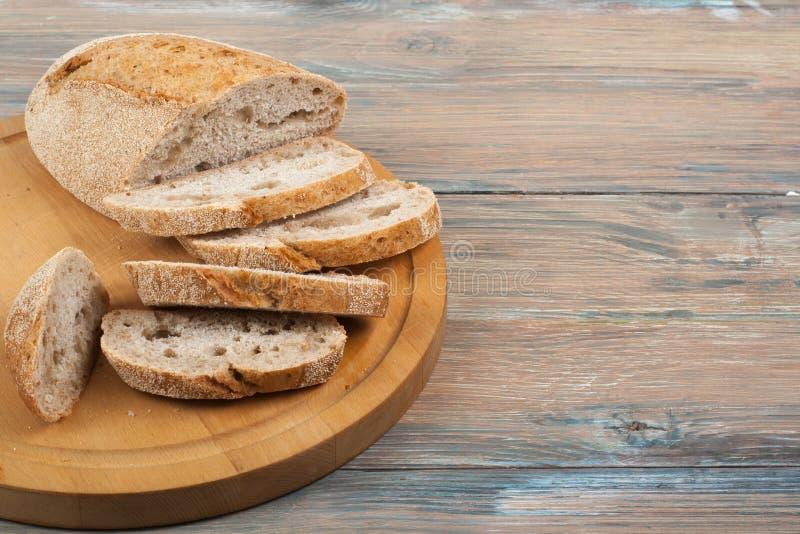 Muchos panes y rollos mezclados del pan cocido en fondo de madera de la tabla foto de archivo