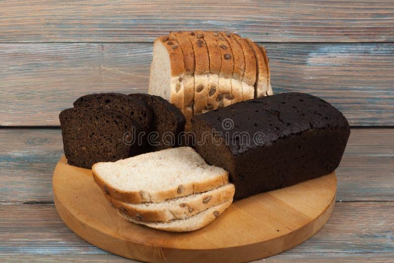 Muchos panes y rollos mezclados del pan cocido en fondo de madera de la tabla imagen de archivo