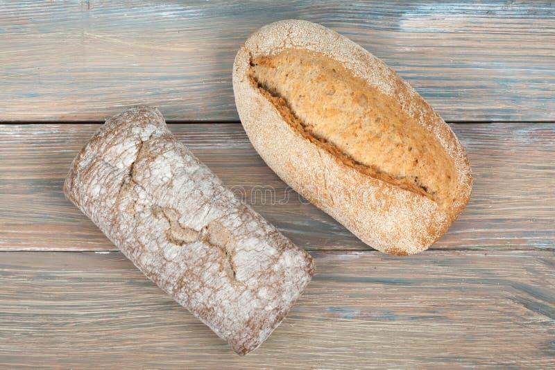 Muchos panes y rollos mezclados del pan cocido en fondo de madera de la tabla Visi?n superior imagenes de archivo