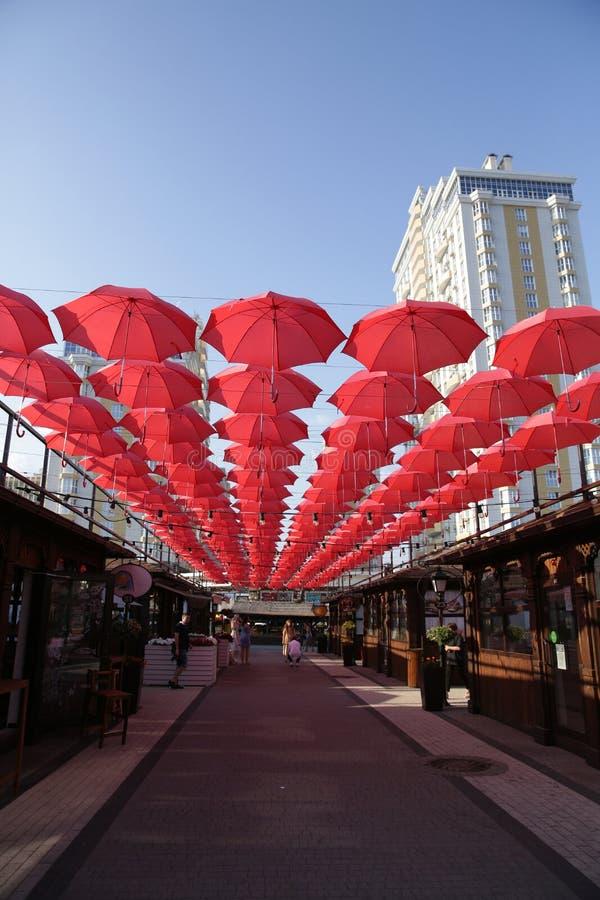 Muchos paraguas coralinos rojos contra el cielo azul y el edificio blanco Fondo abstracto con los paraguas fotografía de archivo