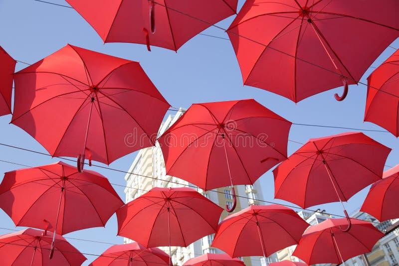 Muchos paraguas coralinos rojos contra el cielo azul y el edificio blanco Fondo abstracto con los paraguas fotos de archivo