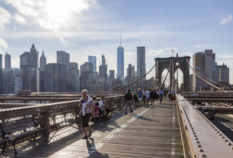 Muchos peatones y ciclistas en la cubierta superior del puente de Brooklyn con Manhattan en el fondo, Nueva York, Estados Unidos imagen de archivo libre de regalías