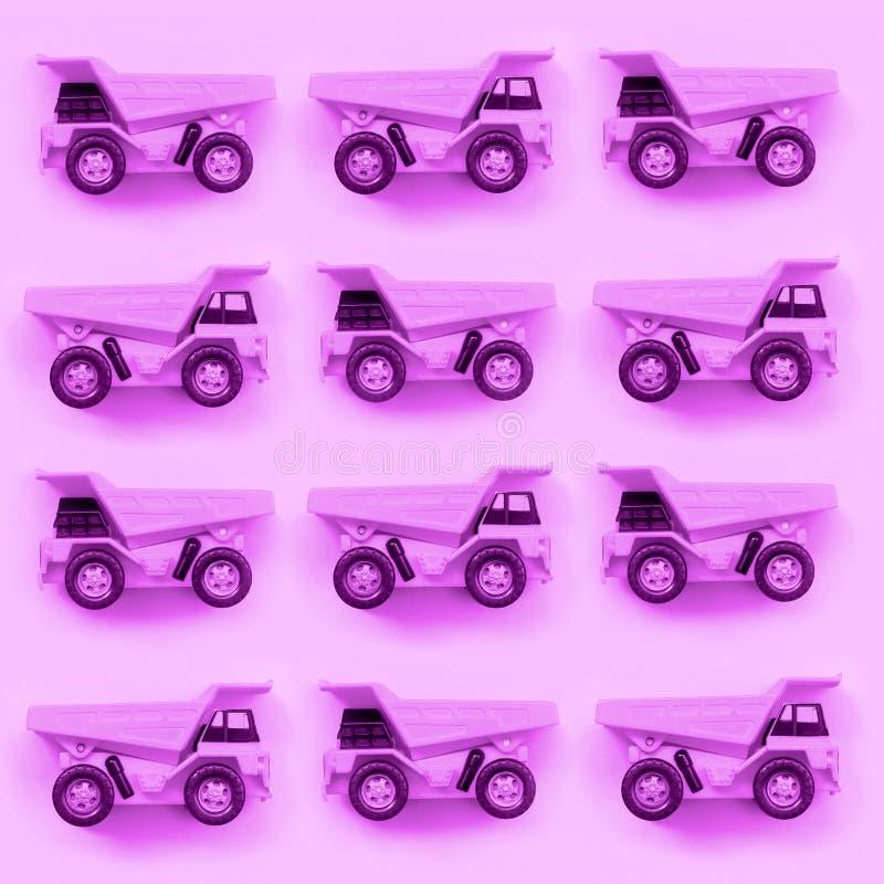 Muchos pequeños camiones púrpuras del juguete en el fondo de la textura del papel púrpura en colores pastel del color de la moda fotografía de archivo