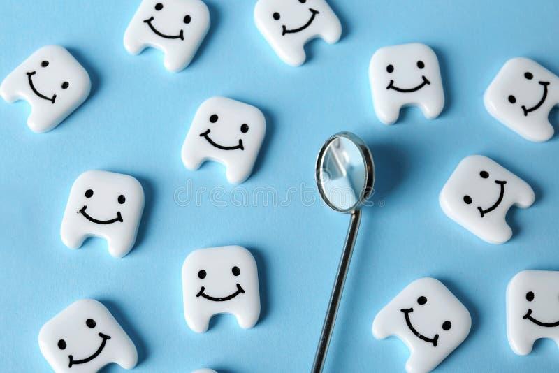 Muchos pequeños dientes plásticos con las caras lindas y espejo de boca en fondo del color fotografía de archivo libre de regalías