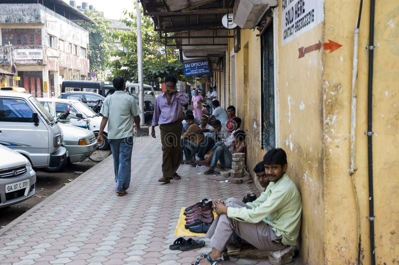 Muchos pobres hombres indios se sientan en la acera cerca del camino y venden algo La India, Goa- 29 de enero de 2009 foto de archivo