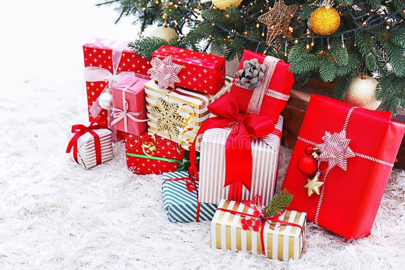 Muchos regalos de la Navidad en piso debajo del ?rbol de abeto imagen de archivo libre de regalías