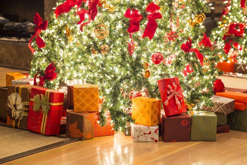 Muchos regalos y árbol de navidad hermoso en piso fotografía de archivo libre de regalías