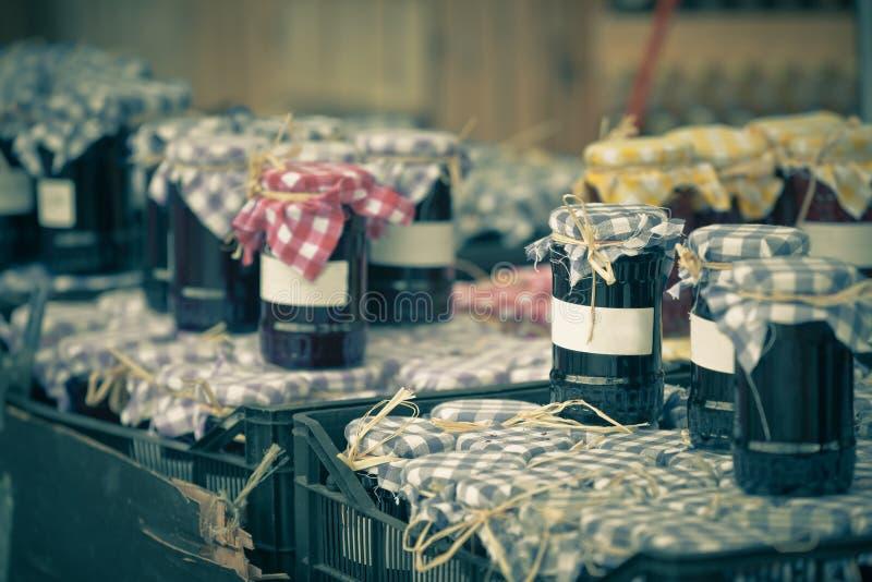 Muchos tarros que preservan con el atasco oscuro en un mercado imagenes de archivo
