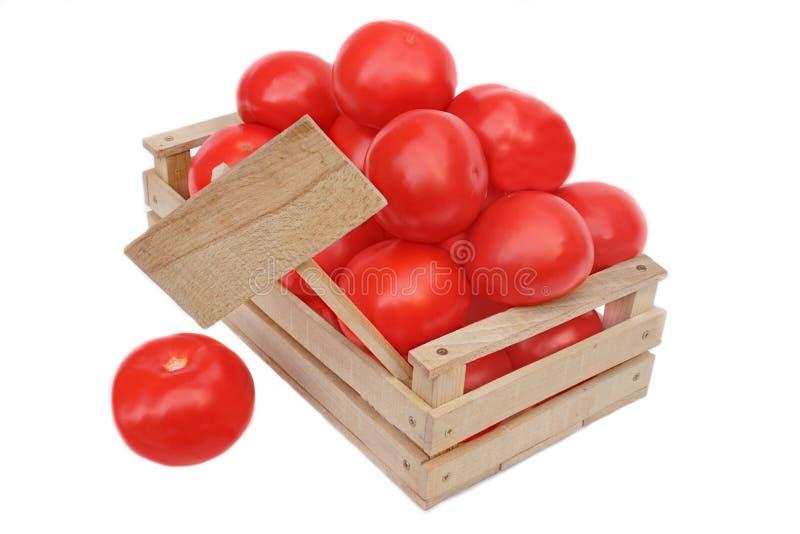 Muchos tomates en caja de madera y precio suben imágenes de archivo libres de regalías