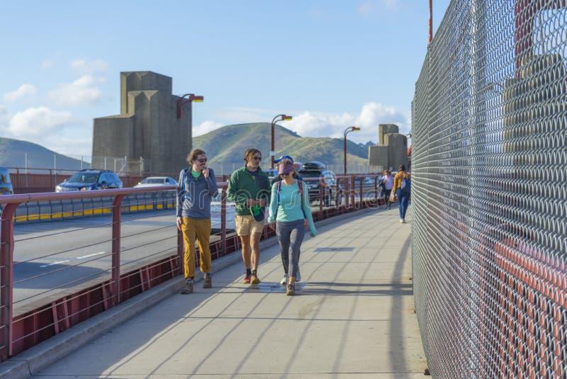 Muchos turistas que caminan encima de puente Golden Gate contra el cielo azul en San Francisco, CA imágenes de archivo libres de regalías