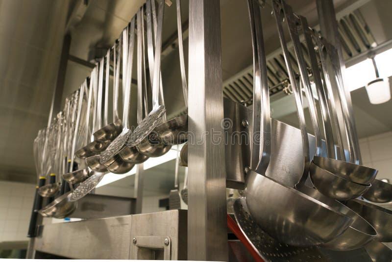 Muchos utensilios y cucharones de la cocina que cuelgan de un estante en una cocina del restaurante imagenes de archivo