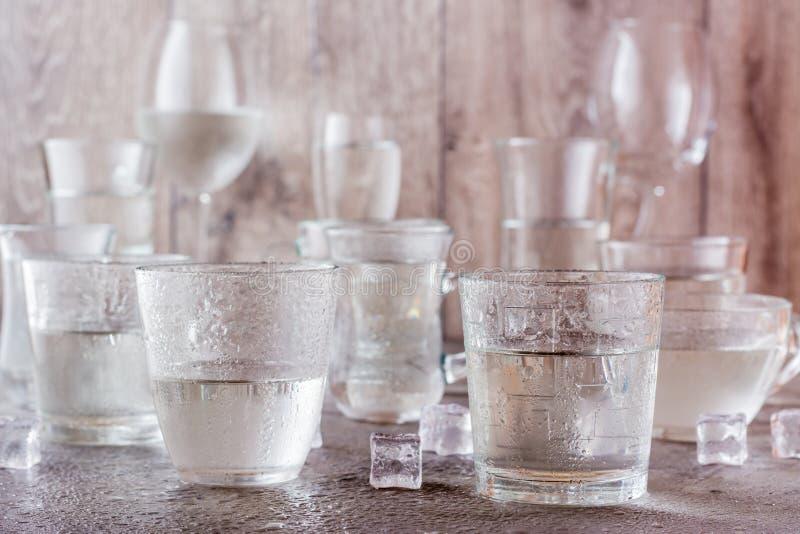 Muchos vasos de agua salpicados con descensos y pedazos de hielo fotos de archivo