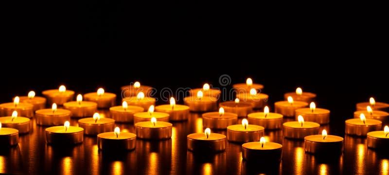 Muchos velas ardiendo con la profundidad del campo baja fotos de archivo