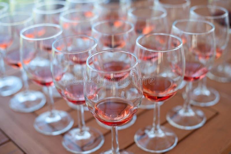 Muchos vidrios con el vino en la tabla para probar imagenes de archivo