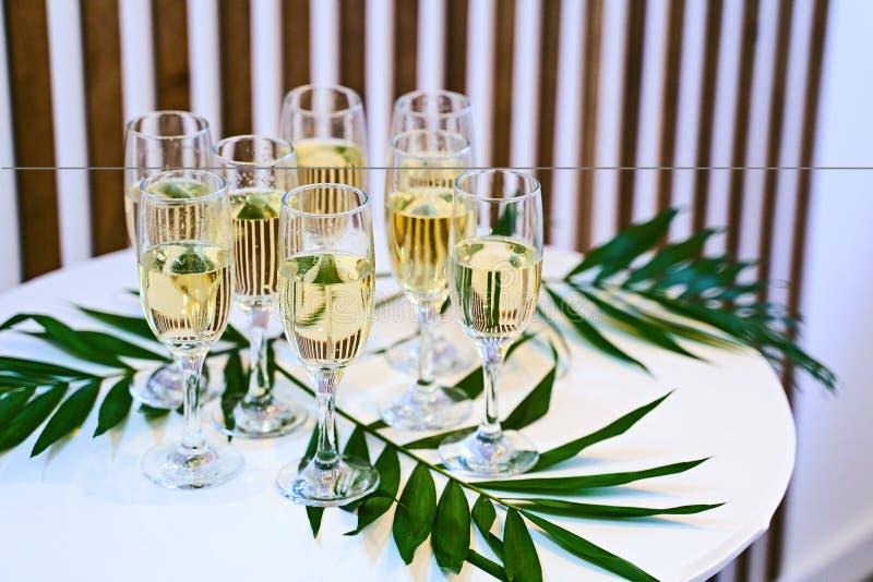 Muchos vidrios del champán en la tabla adornada de la presentación imagen de archivo
