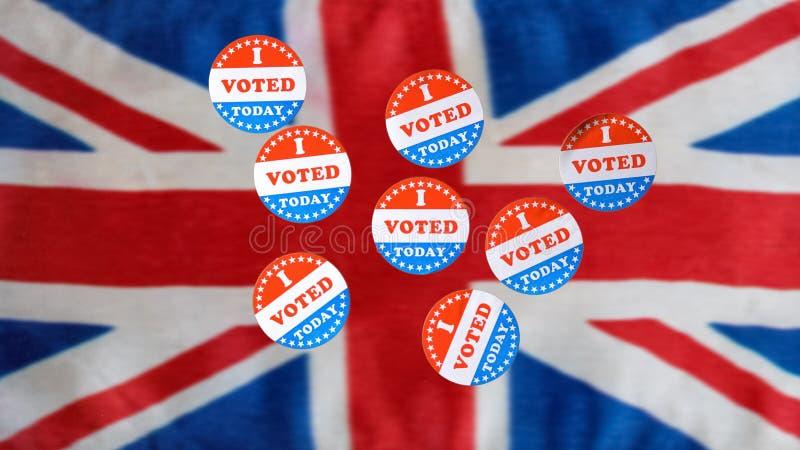 Muchos voté hoy las etiquetas engomadas de papel en bandera BRITÁNICA fotografía de archivo