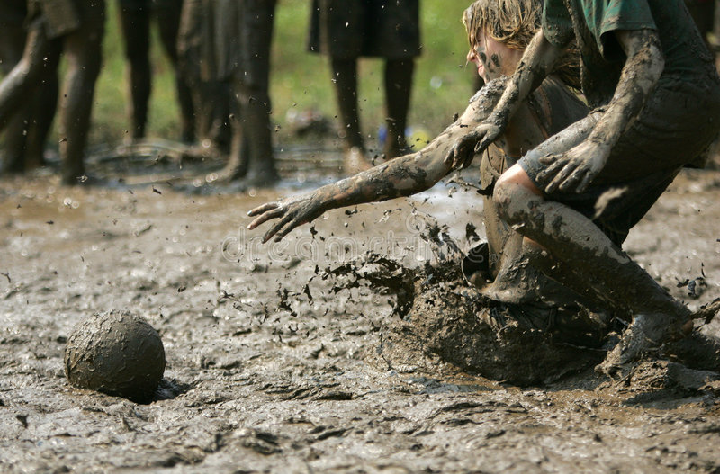 Mud bowl #2. Kids have fun playing catch ball at a local mud field