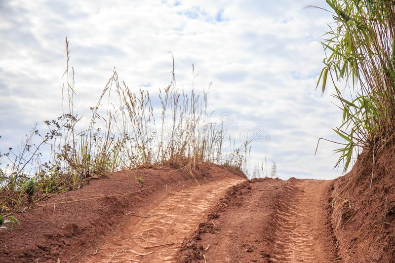 Mud or dirty road on the mountain hill with sky clouds of country side. royalty free stock images