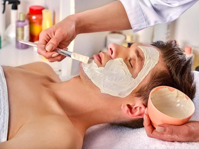 Mud facial mask of woman in spa salon. Face massage. Mud facial mask of men in spa salon. Massage with clay full face. Girl on with therapy room. Man lying on royalty free stock photography