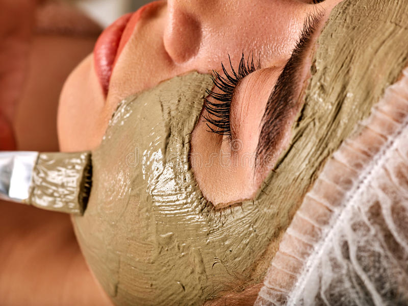 Mud facial mask of woman in spa salon. Massage with clay full face. Girl on with therapy room. Beautician with brush therapeutic procedure. Mask made of