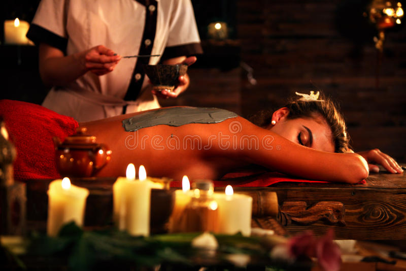 Mud mask of woman in spa salon. Back massage . Mud mask of women in spa salon. Back massage with clay full body . Girl on interior with candles foreground in royalty free stock image