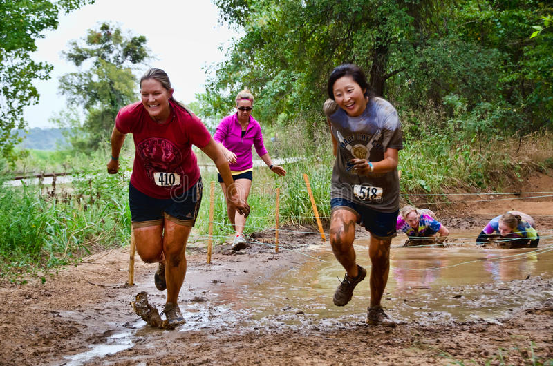 Mud race participants passing through a mud pit stock image