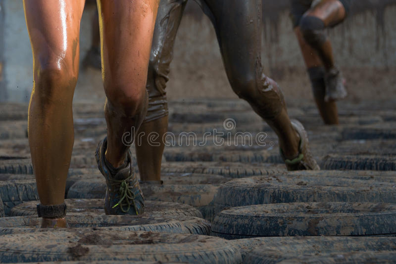 Mud race runners. Tries to make it through the tire trap royalty free stock photos
