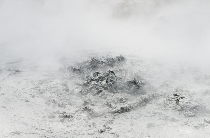 Mud volcanic geyser. Volcanic crater with bubbling water mixed with gray mud covered by the thick puffy white smoke, Indonesia royalty free stock image