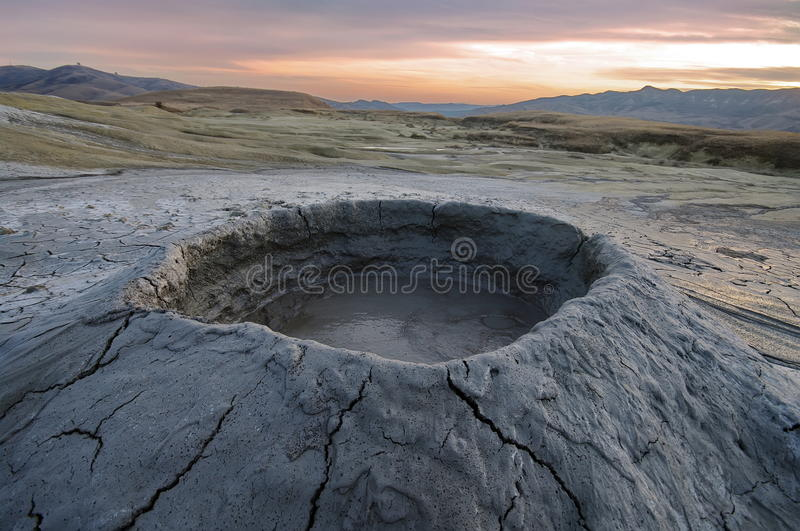 Bubbling mud. Mud volcano at sunset - landmark attraction in Buzau, Romania.  stock photo