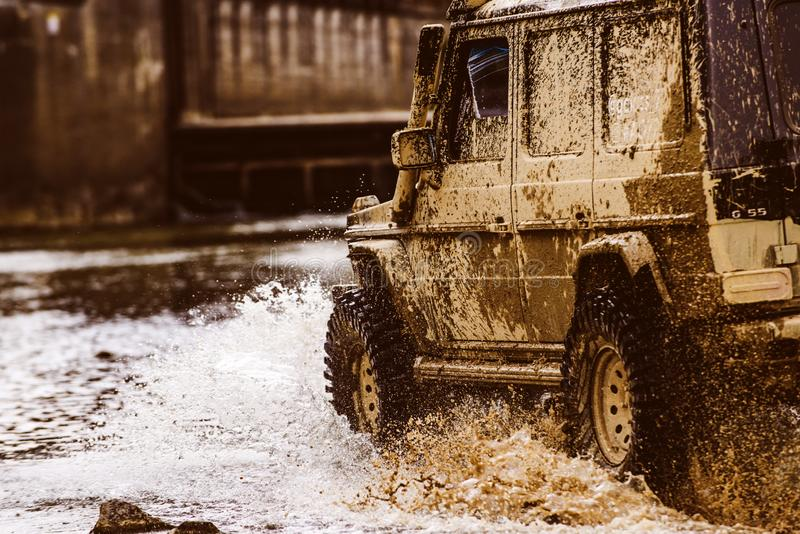 Mud and water splash in off the road racing. Bottom view to big offroad car wheel on country road and mountains backdrop. Off-road vehicle goes on the mountain stock photography