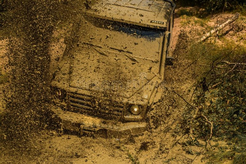 Mud and water splash in off-road racing. Expedition offroader. Best Off Road Vehicles. Offroad vehicle coming out of a. Mud hole hazard. Tracks on a muddy field stock images