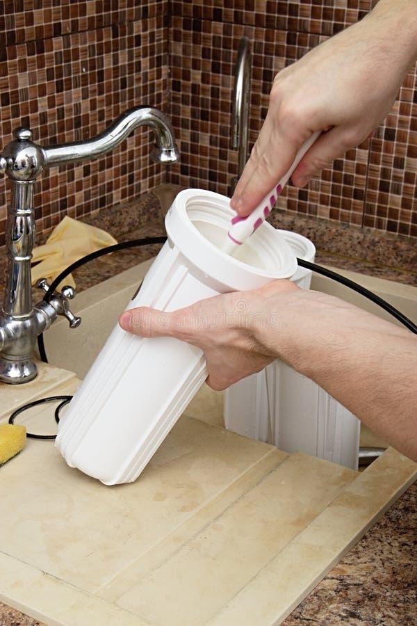 Mudança do encanador o filtro de água instalando a osmose na casa a mão masculina gerencie o cartucho a mão masculina lava a fotos de stock