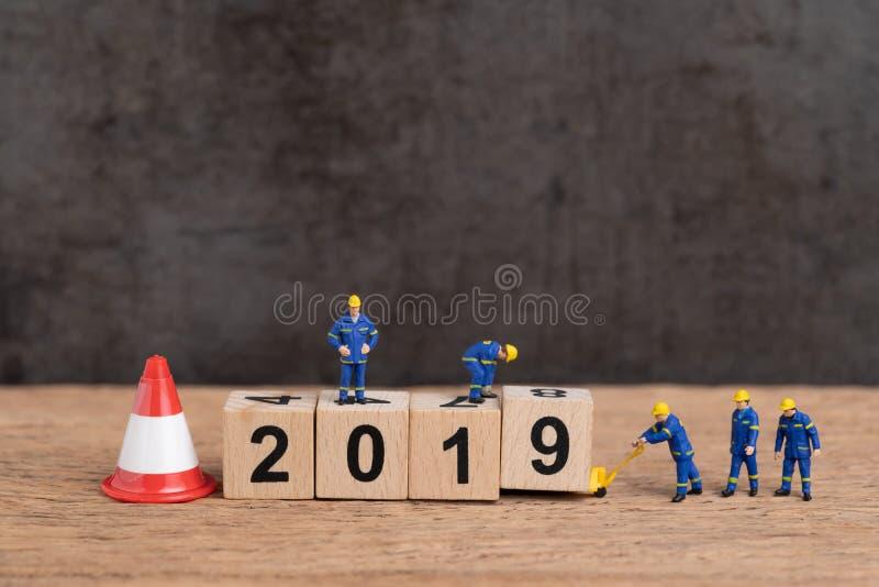 Mudança nova do ano do ano 2019 ou apenas conceito terminado, trabalhadores diminutos dos povos que constroem o bloco de madeira  foto de stock