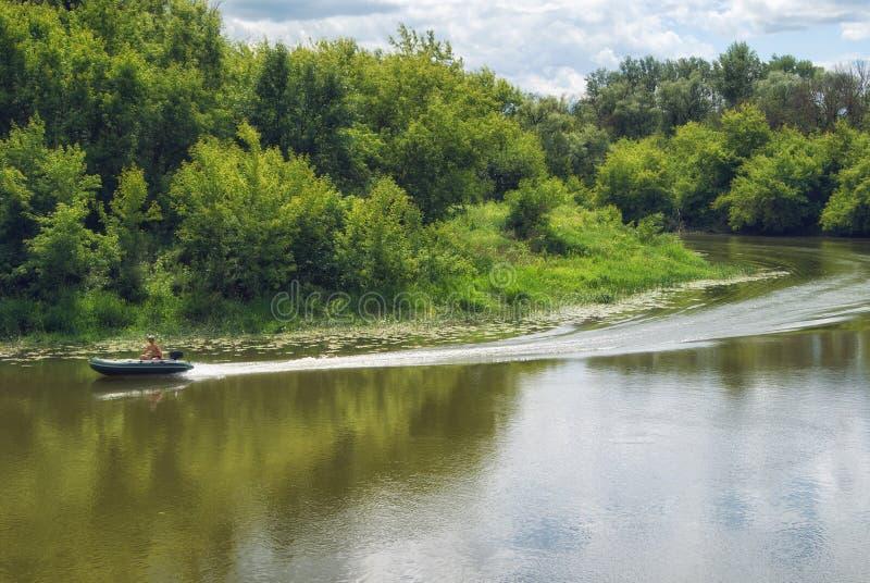 Mudanza encendido de un barco de motor en un río con las costas boscosas fotografía de archivo libre de regalías