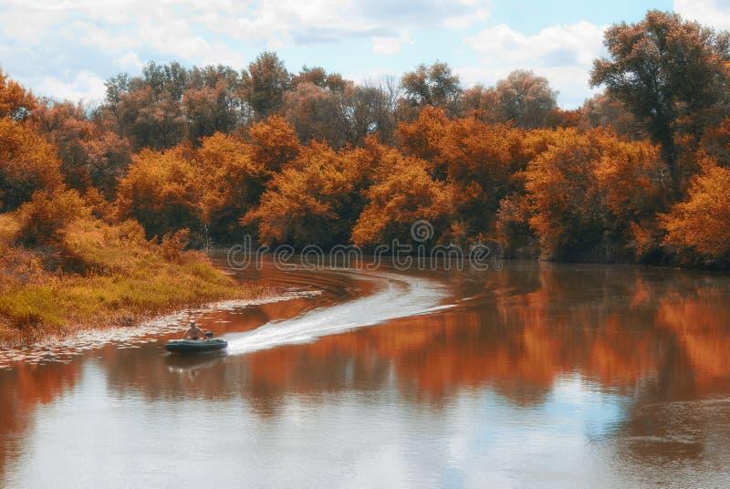 Mudanza encendido de un barco de motor en un río con las costas boscosas foto de archivo