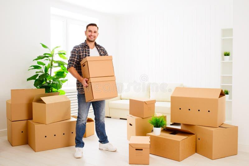 Mudanza a un nuevo apartamento hombre feliz con las cajas de cartón fotos de archivo