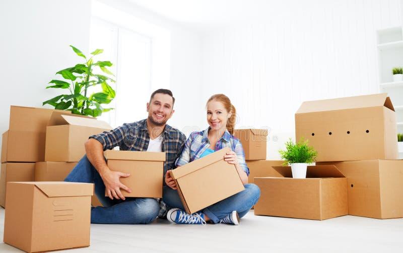 Mudanza a un nuevo apartamento Pares de la familia y caja de cartón felices fotografía de archivo libre de regalías