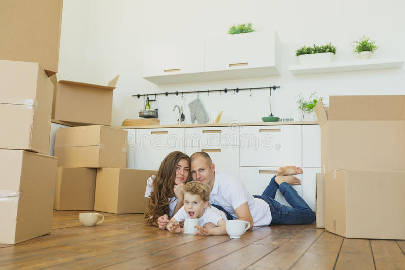 Mudanza a un nuevo hogar Familia feliz con las cajas de cartón foto de archivo libre de regalías