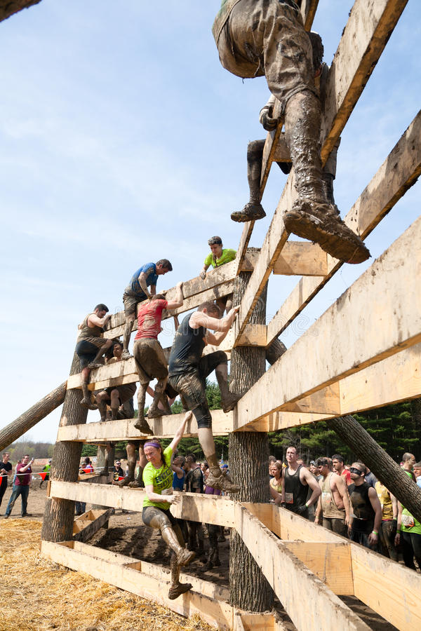 Mudder dur : Coureurs s'élevant au-dessus d'un obstacle photo libre de droits