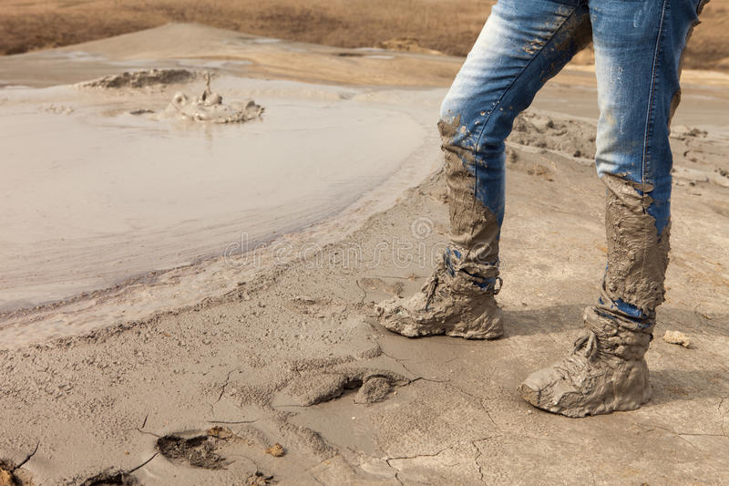 muddy and dirty hiking boots and blue jeans stock photo