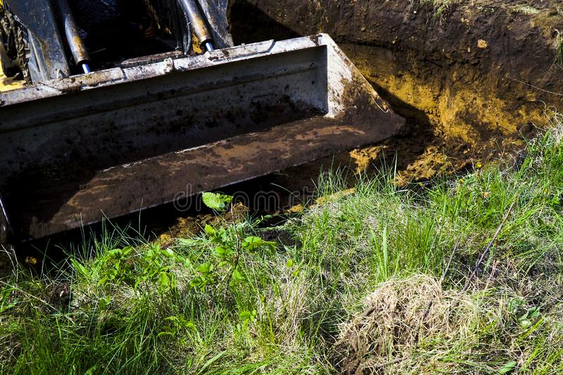 Muddy excavator bucket going to dig soil in grassy field in countryside royalty free stock image