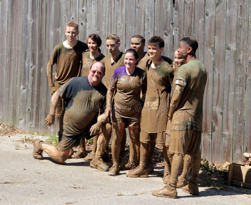 Muddy Group de poses dos povos para a imagem após ter terminado uma corrida da lama foto de stock