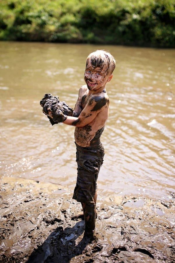 Muddy Little Boy Child Laughing como él nada y juega afuera adentro fotos de archivo