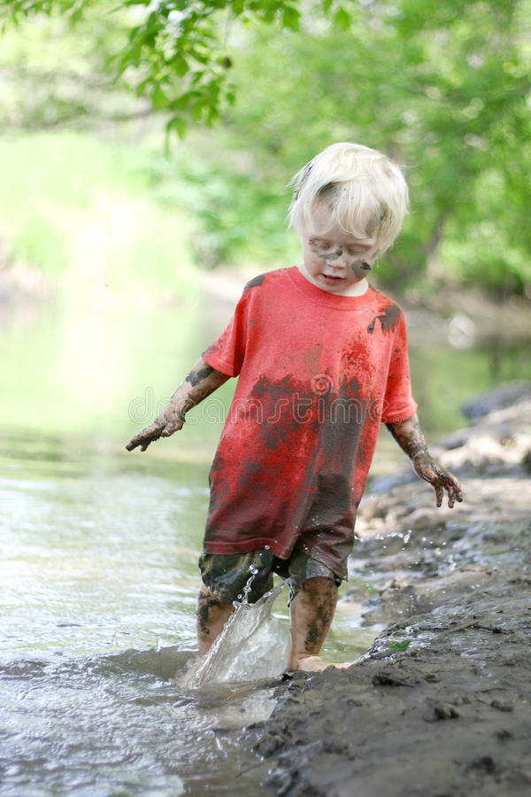 Muddy Little Boy Playing Outside in the River. A cute, dirty little boy child is playing outside, splashing in a river on a muddy beach on a summer day stock images